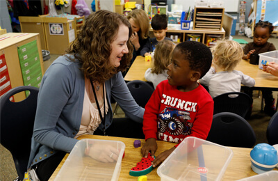 Meigen Fink, preschool teacher at Kirkwood Elementary School in Iowa City, responds to a student's inquiry during a morning activity.