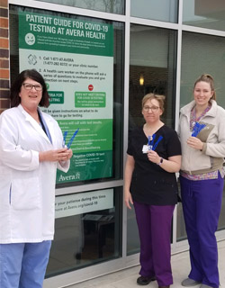Three Avera Medical employees standing outside the facility in front of the windows, holding and displaying mask ear savers.