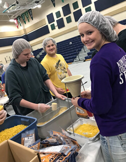 Sumner-Fredericksburg high school students measure and package ingredients into bags. Each 'taco mac' bag contains enriched pasta, textured vegetable protein (soy flour), and a vitamin and mineral fortified cheese mix. One bag is enough for six servings.