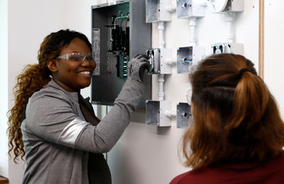 Students learn how to wire and install an electrical outlet.