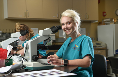 4.	Female student participating in Indian Hills Community College Health Sciences Program, shown in lab setting utilizing a microscope.