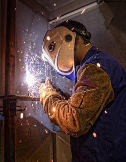 3.	Student in Indian Hills Community College Welding Technology Program, shown working on a welding project, wearing welding mask and gloves.